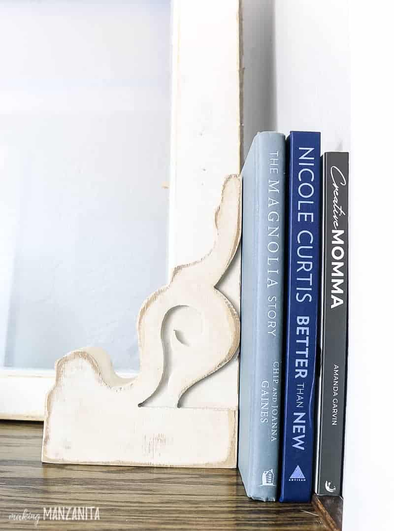 White distressed farmhouse corbel used as a bookend holding up three books