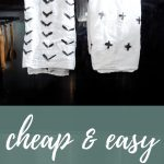 Two custom tea towels painted with arrows and crosses hanging on oven door with text overlay that says cheap & easy DIY tea towels