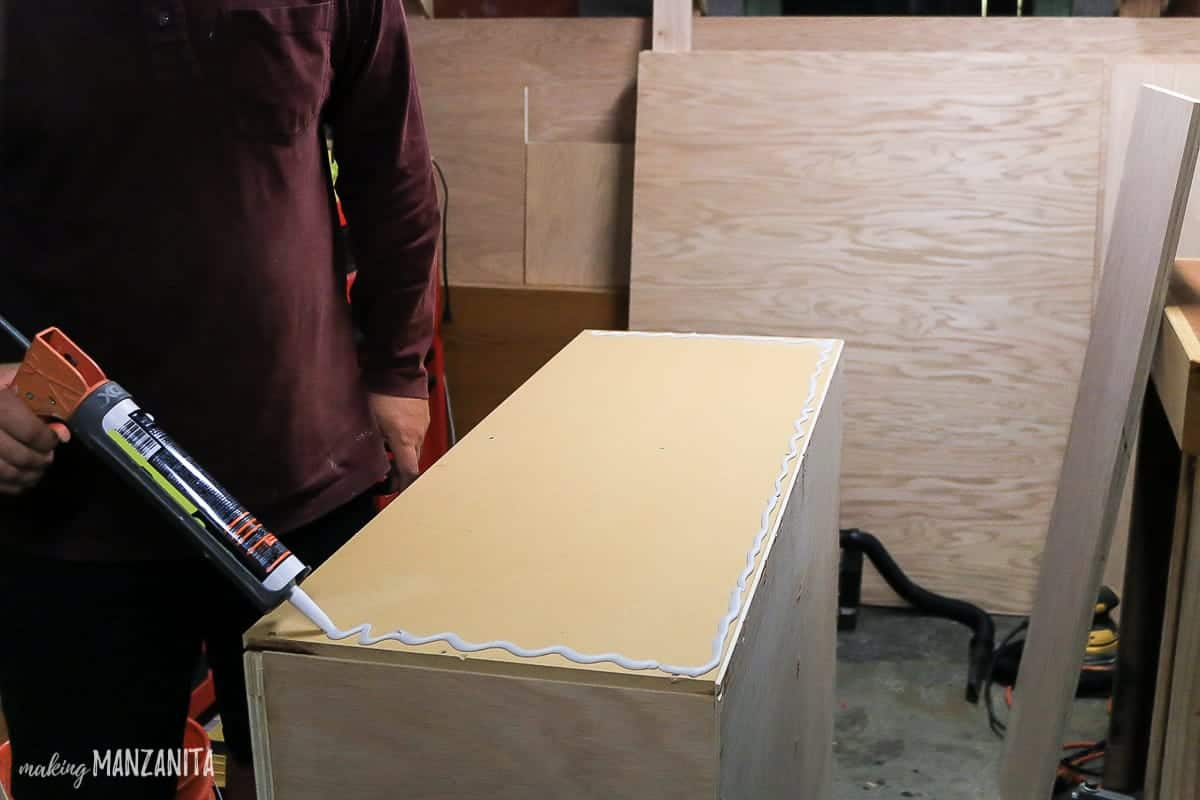 Man adding construction adhesive to the top of cabinet before setting on wood countertop