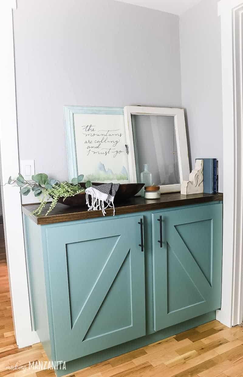 Blue green paint hallway cabinet with farmhouse style, x barn door fronts, oil rubbed bronze hardware, stained wood top and decorated on the top with farmhouse decor
