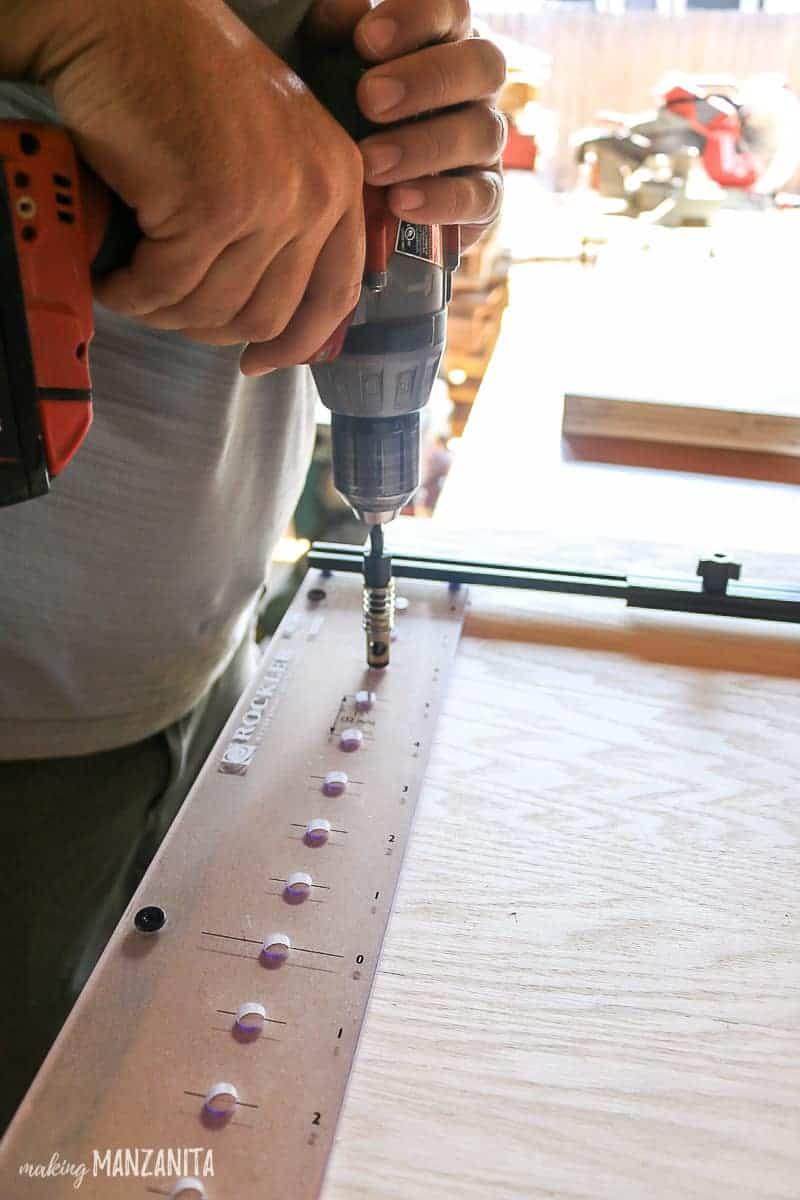 Man drilling holes for adjustable shelves using Rockler's pro shelf drilling jig