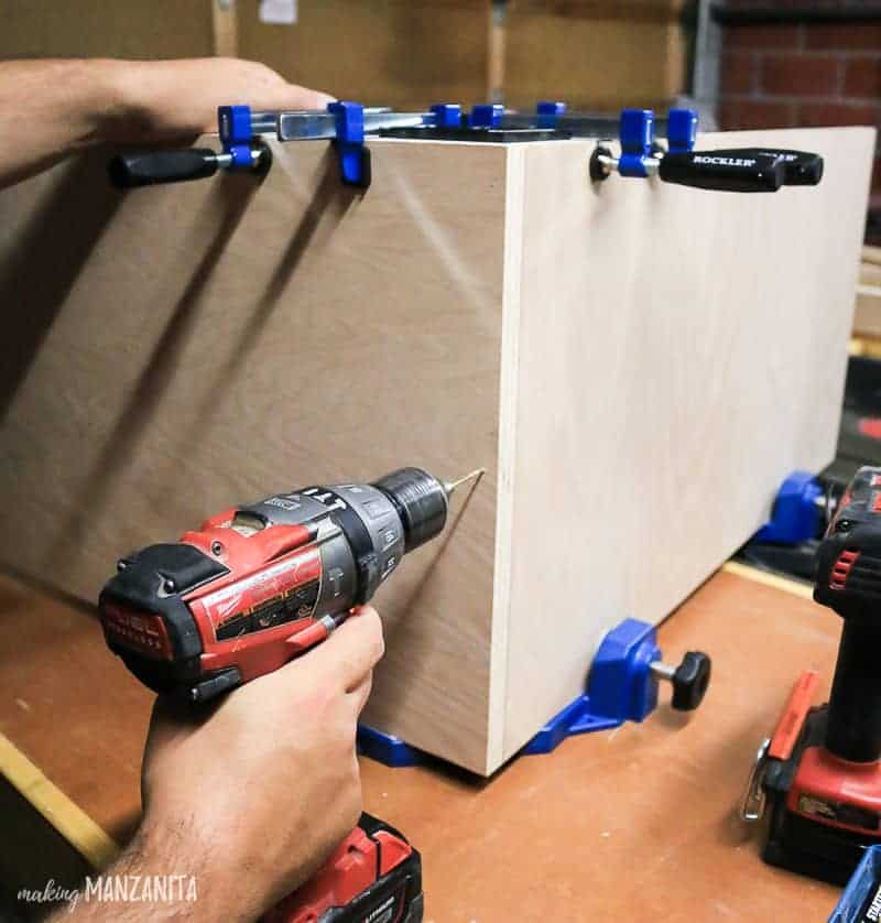 man screwing base cabinet box together with jigs clamped on to keep the corner square while assembling