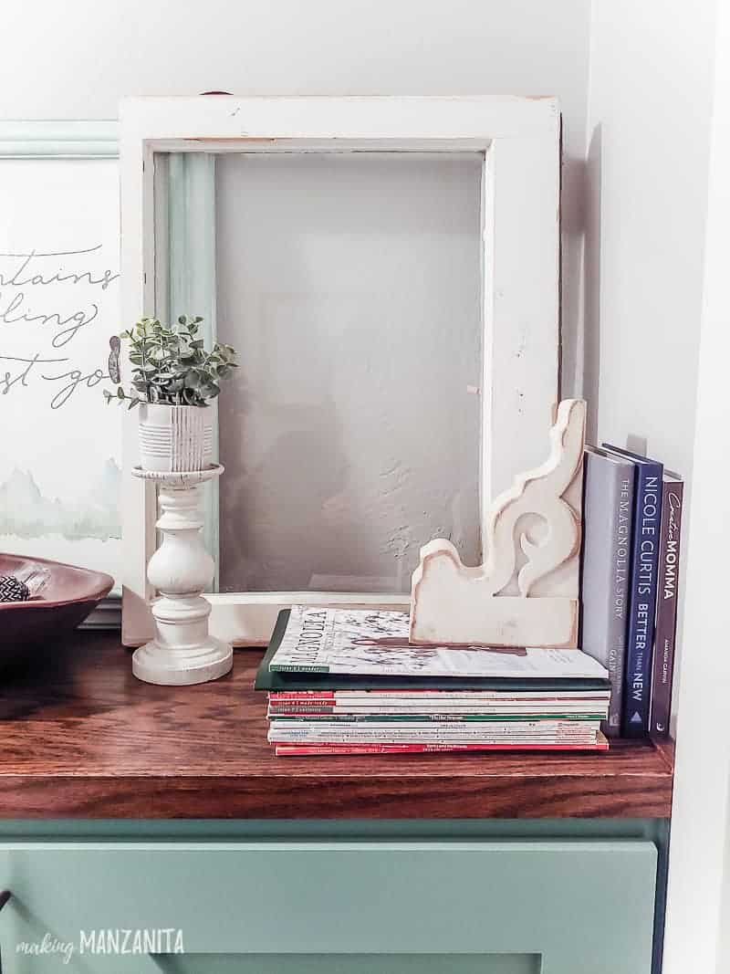 Farmhouse candlestick with faux plant staged on top of cabinet with corbel used as bookend in front of vintage window and framed art