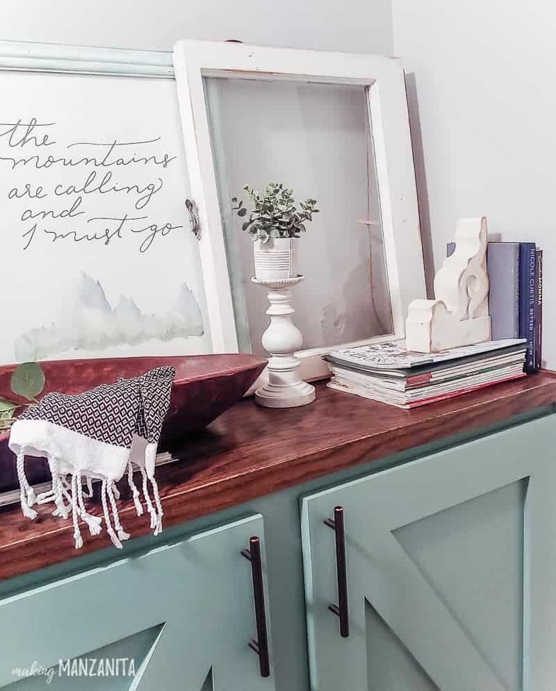Farmhouse style vignette staged on a cabinet top with wooden dough bowl, corbel, candlestick with faux plant, book, vintage window and framed art that says the mountains are calling and I must go