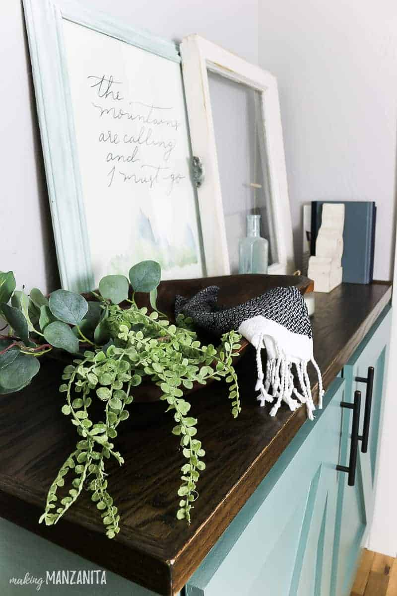 Faux greenery in wooden bowl on cabinet top decorate with farmhouse style decor