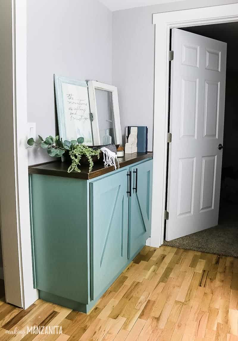 Blue green painted cabinet built-in on the hallway for extra storage and decorated with frames, vintage window, books and a wooden dough bowl with faux greenery