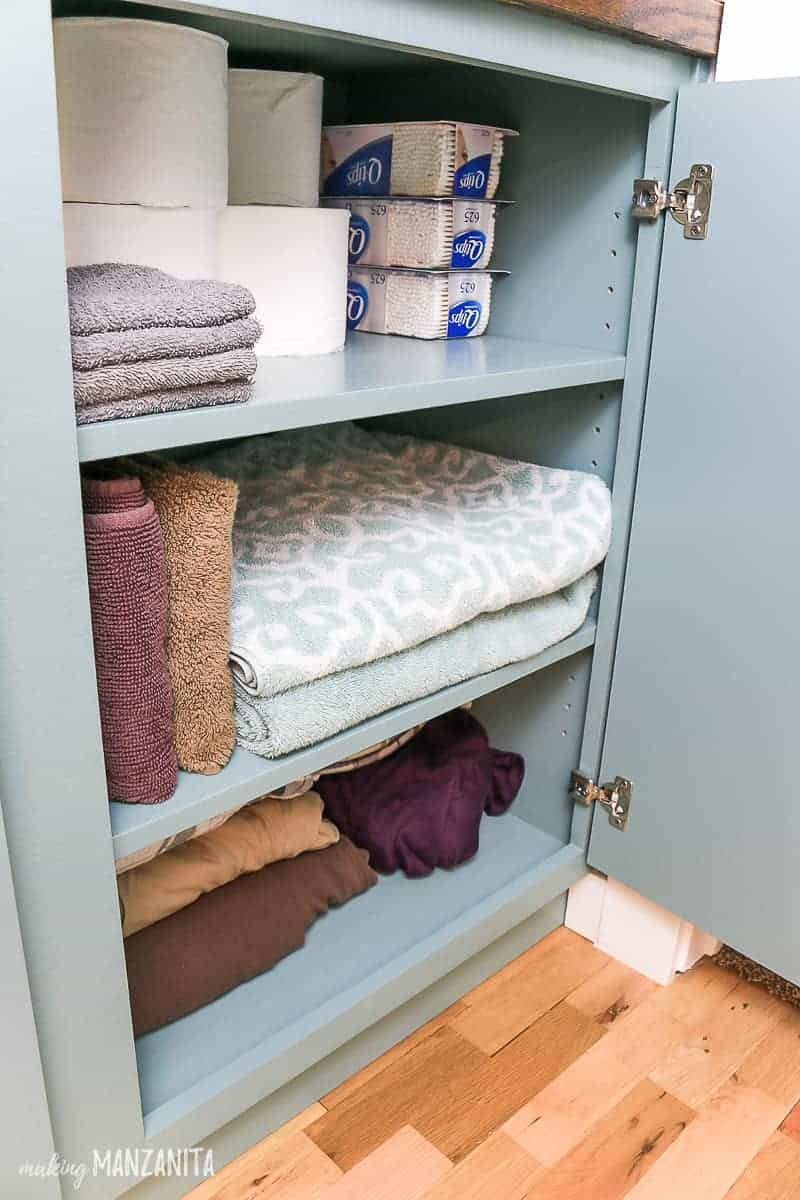 Open door for hallway cabinet showing extra toilet paper rolls, Q tips, towels, washcloths and sheets