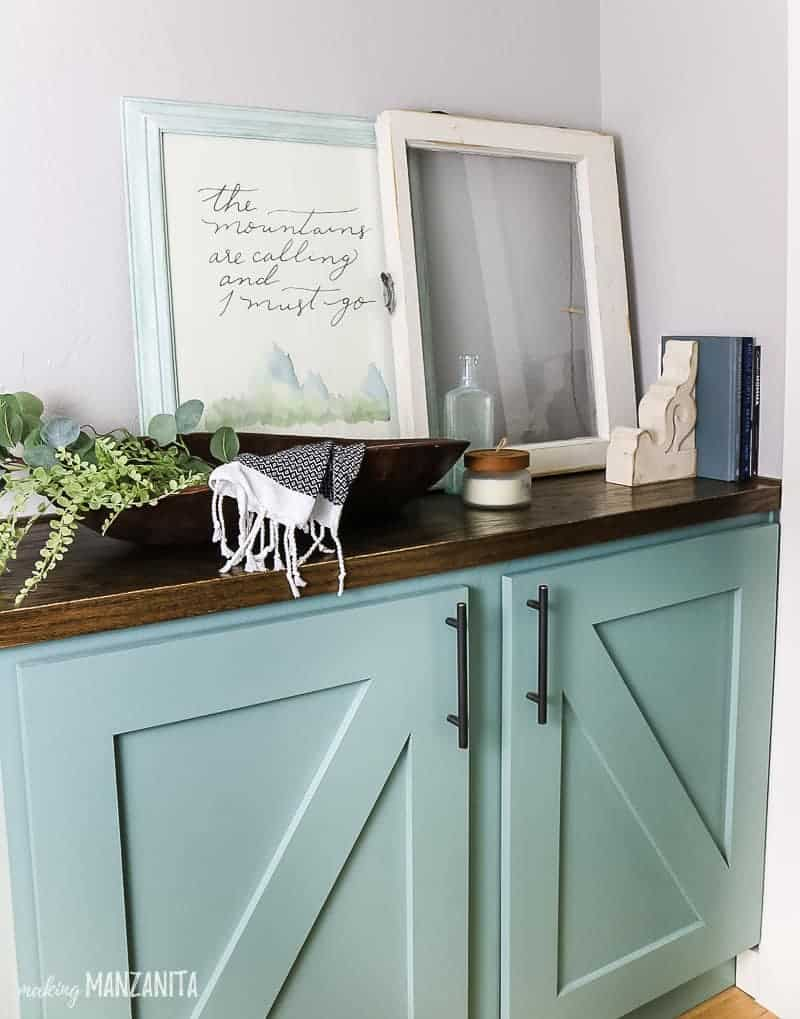 Green painted cabinet built into hallway with farmhouse decor on the top