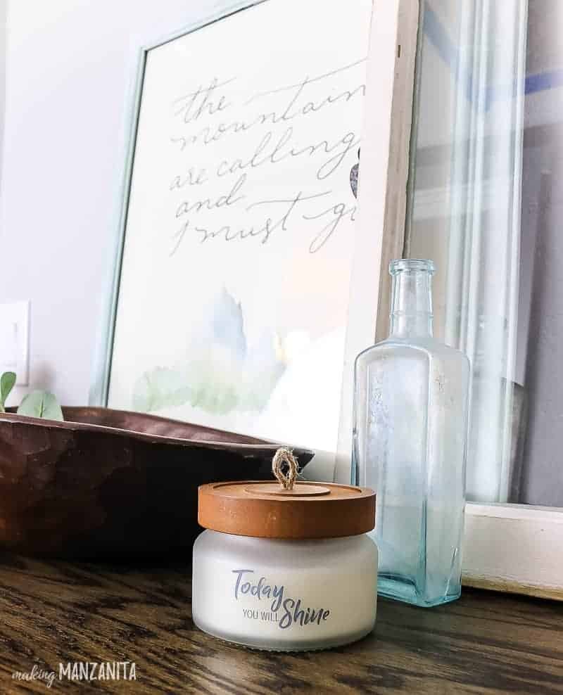 Cabinet top s decorated using framed art prints, an old window, vintage glass bottles, candle with wood top and a wooden dough bowl full for farmhouse faux greenery