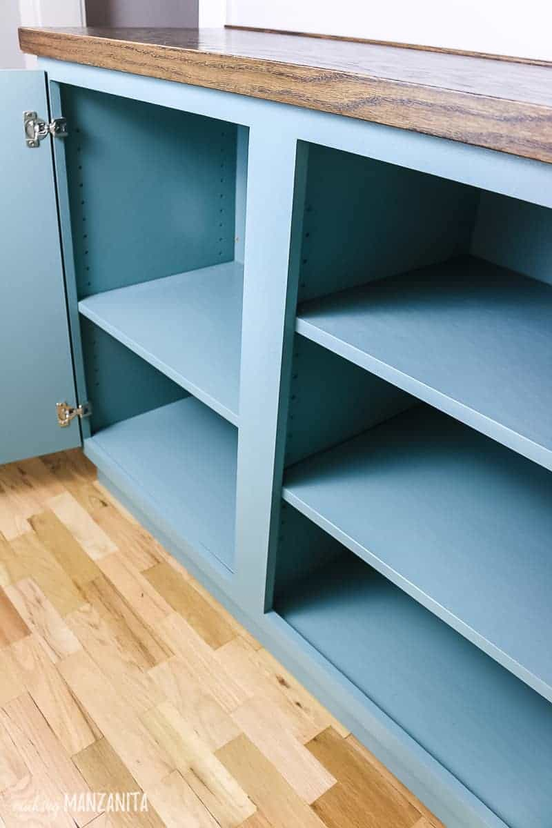 Doors open on a hallway cabinet painted blue green with adjustable shelves