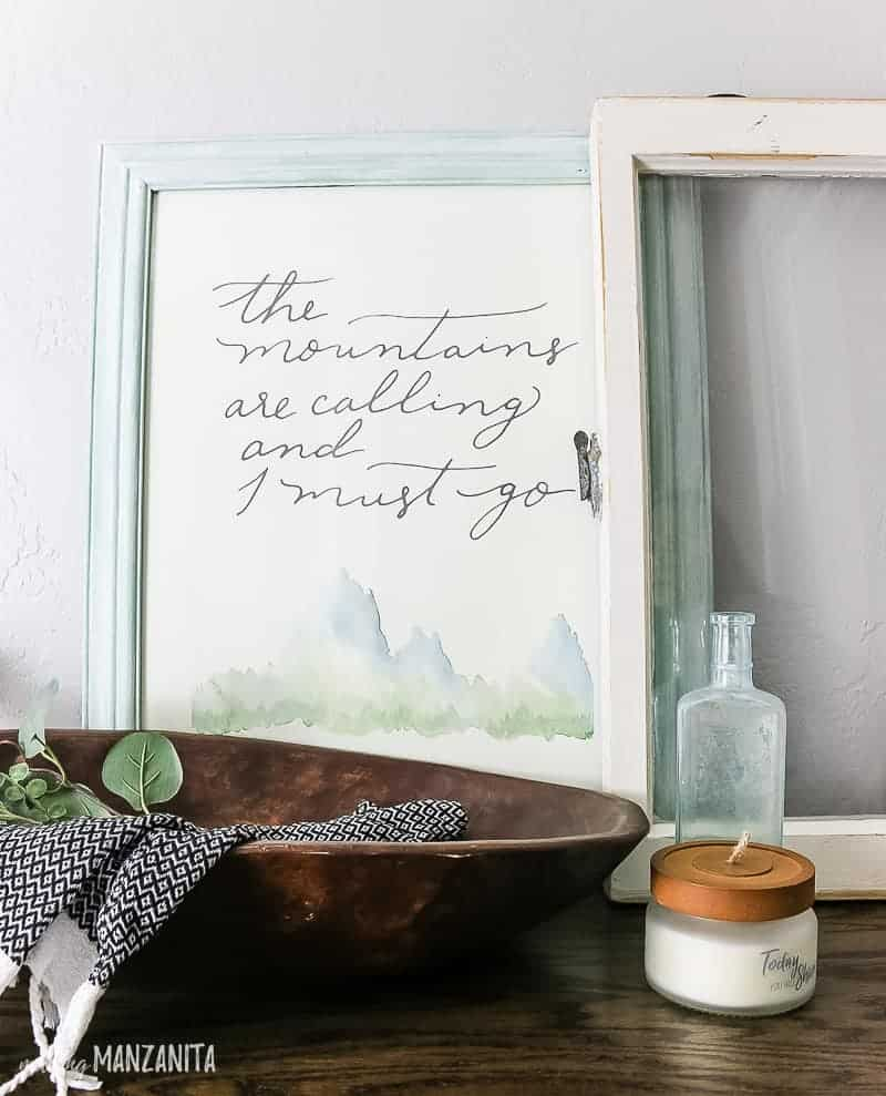 Framed print that says the mountains are calling and I must go leaned against the wall layered with a vintage window on a cabinet top staged with farmhouse style decor