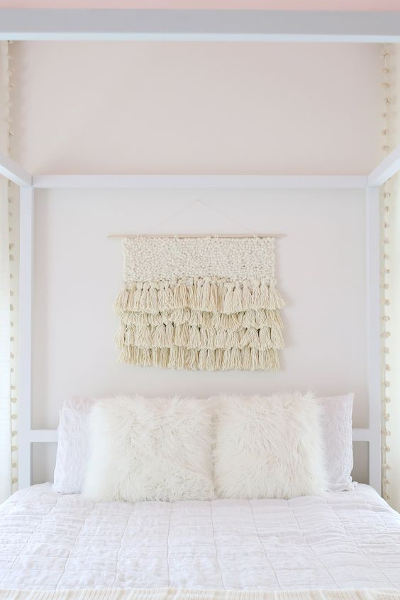 Ivory colored yarn wall hanging with texture and layers of tassels hanging above bed as decor