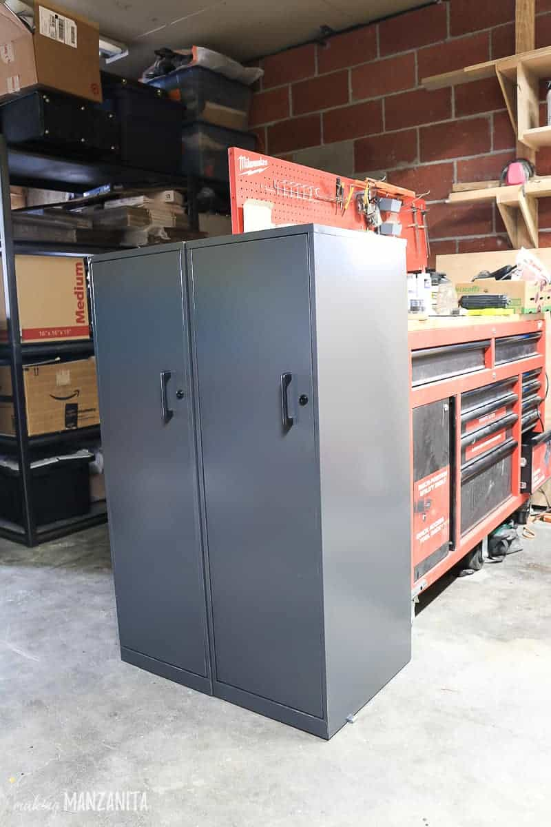 Two gray metal cabinets with locks in garage workshop side by side next to a tool bench