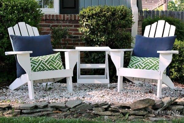 White restored Adirondack chairs sitting outside with blue and green throw pillows
