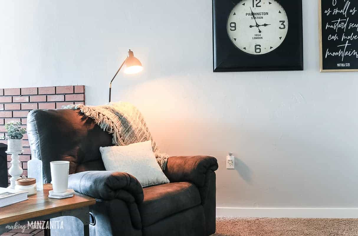 Black modern farmhouse floor lamp behind recliner with blanket draped on back and white throw pillow in cozy living room with industrial clock on wall