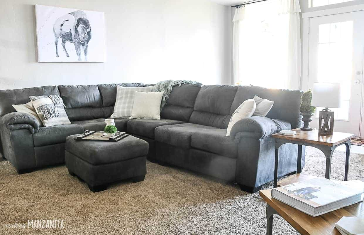 Big comfy cozy sectional couch with farmhouse throw pillows and matching ottoman, light gray wall paint color, buffalo wall art and white simple curtains