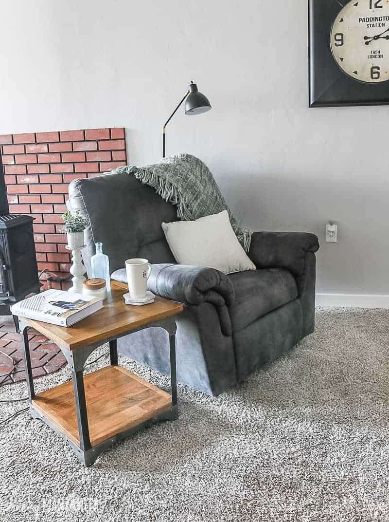 Gray recliner with green blanket and white pillow, industrial side table sitting next to it and brick fireplace shown behind the recliner