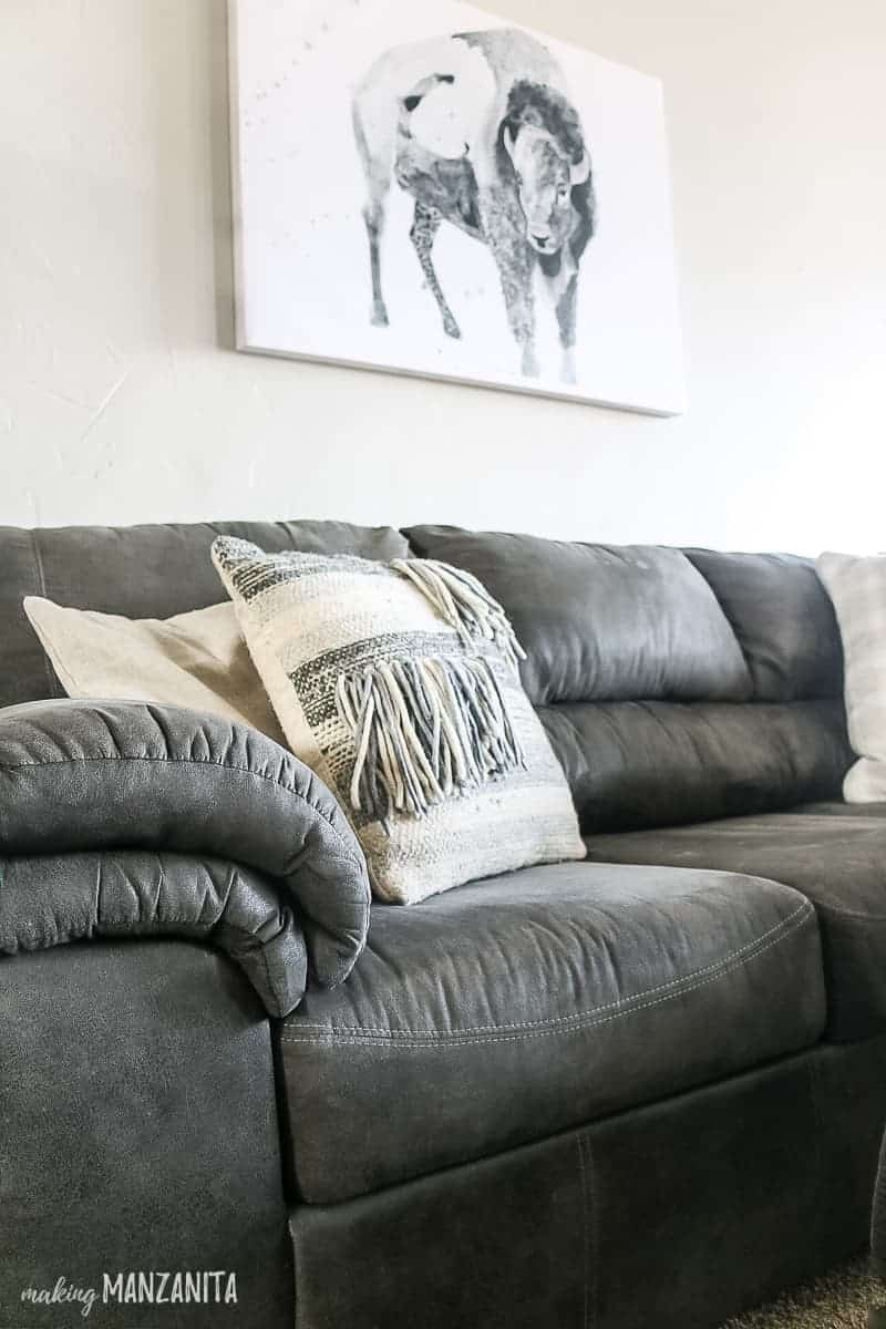 Gray and white boho throw pillow on gray couch with buffalo wall art hanging above