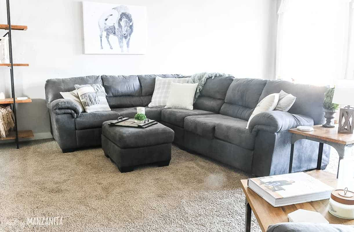 Big comfy gray sectional couch in cozy living room with light gray walls, neutral throw pillows, an ottoman with coffee tray and a buffalo wall painting