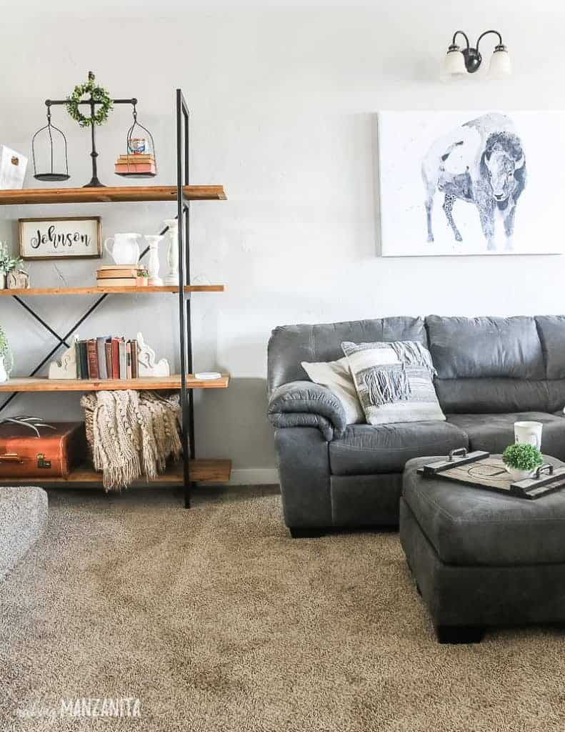 Farmhouse decorated living room with gray couch and ottoman with buffalo watercolor art on wall above couch and shelving unit next to couch decorated with farmhouse style vintage decor like old books, vintage sale, white farmhouse pitcher, candleholders and big wicker basket for blanket storage with light gray painted walls with Behr Chic gray paint color