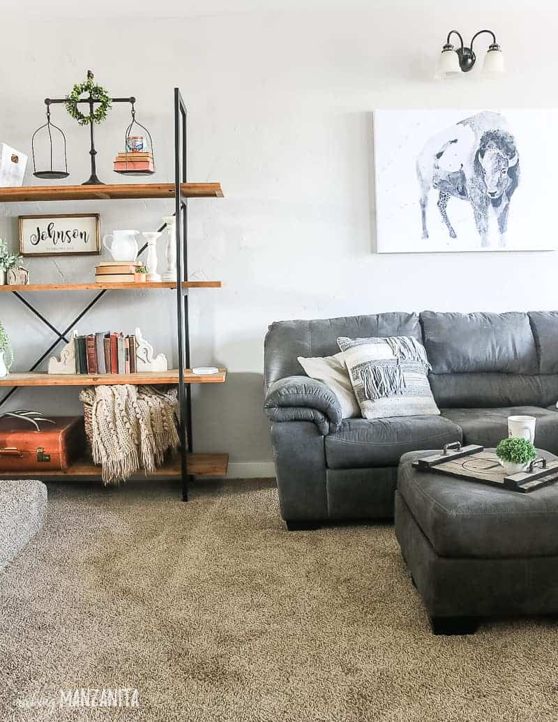 Cozy living room showing farmhouse decorated shelves, gray sectional couch with throw pillows and matching gray ottoman and watercolor buffalo wall art with boho style