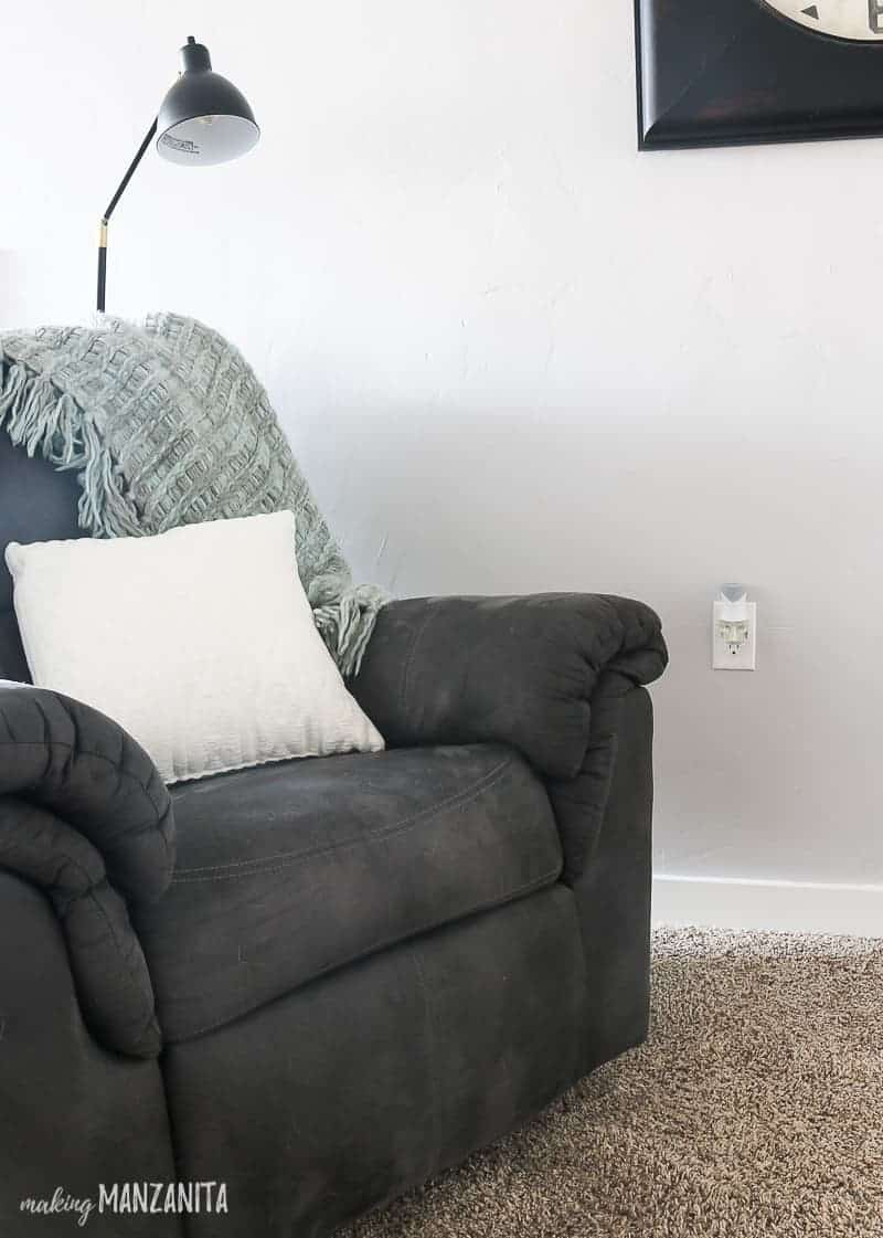 Recliner with blanket draped over the back and white throw pillow with gray paint color on walls and Renuzit air freshener plugged into the wall