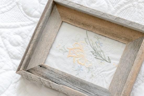 Barnwood frame holding vintage inspired embroidery art