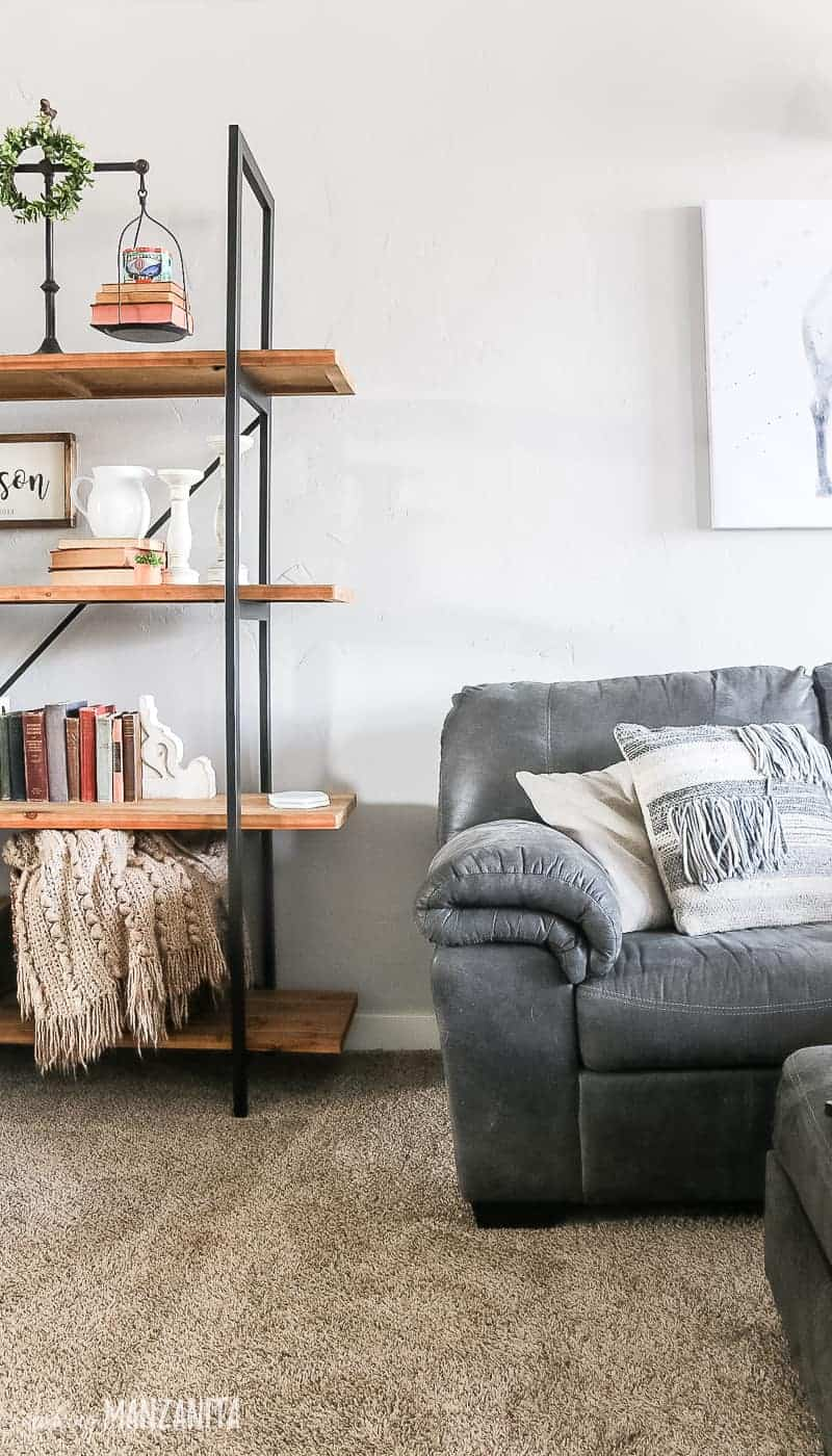 End of gray sectional couch with neutral throw pillows and corner of shelving unit decorated with modern farmhouse decor