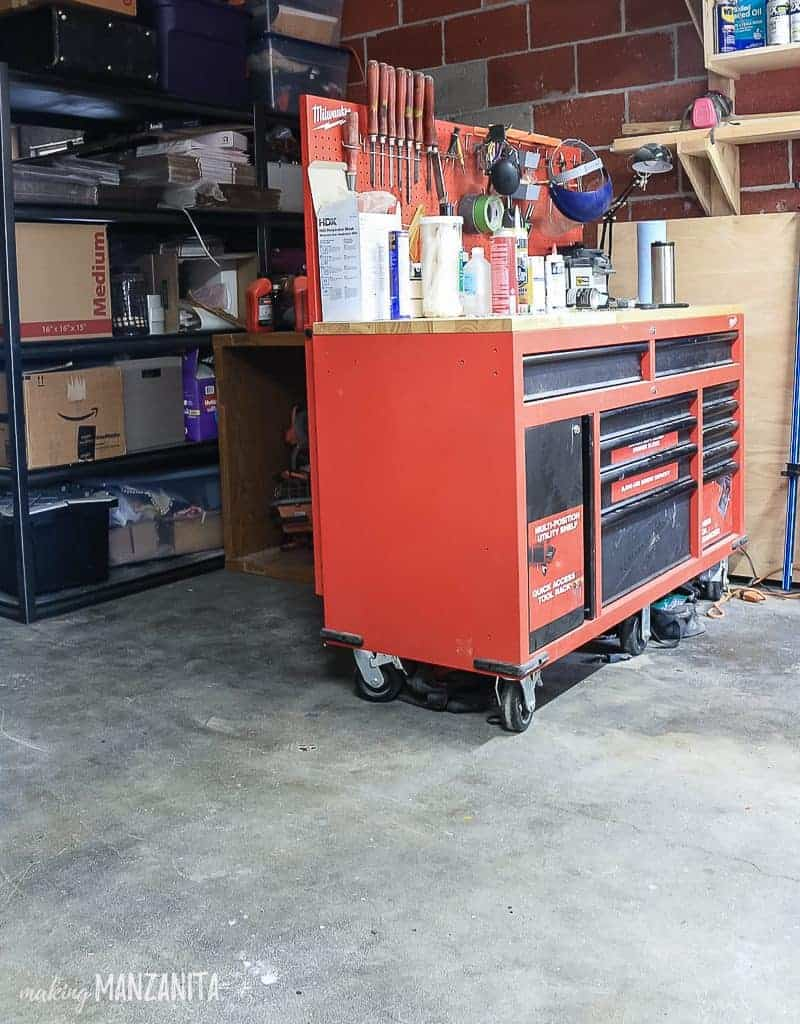 Red tool storage and workbench in garage with concrete floor and a blank space