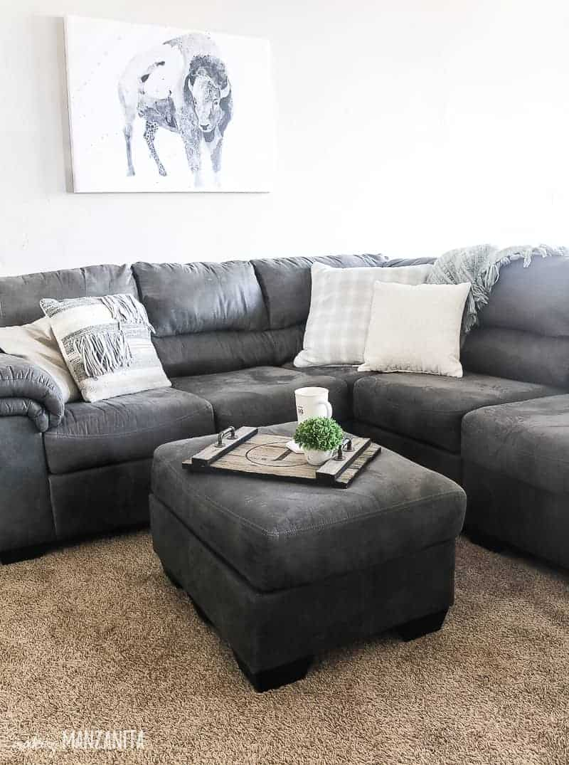 Corner of dark gray sectional couch with throw pillows with boho farmhouse style and matching gray ottoman with wood tray holding coffee cup and mini plant