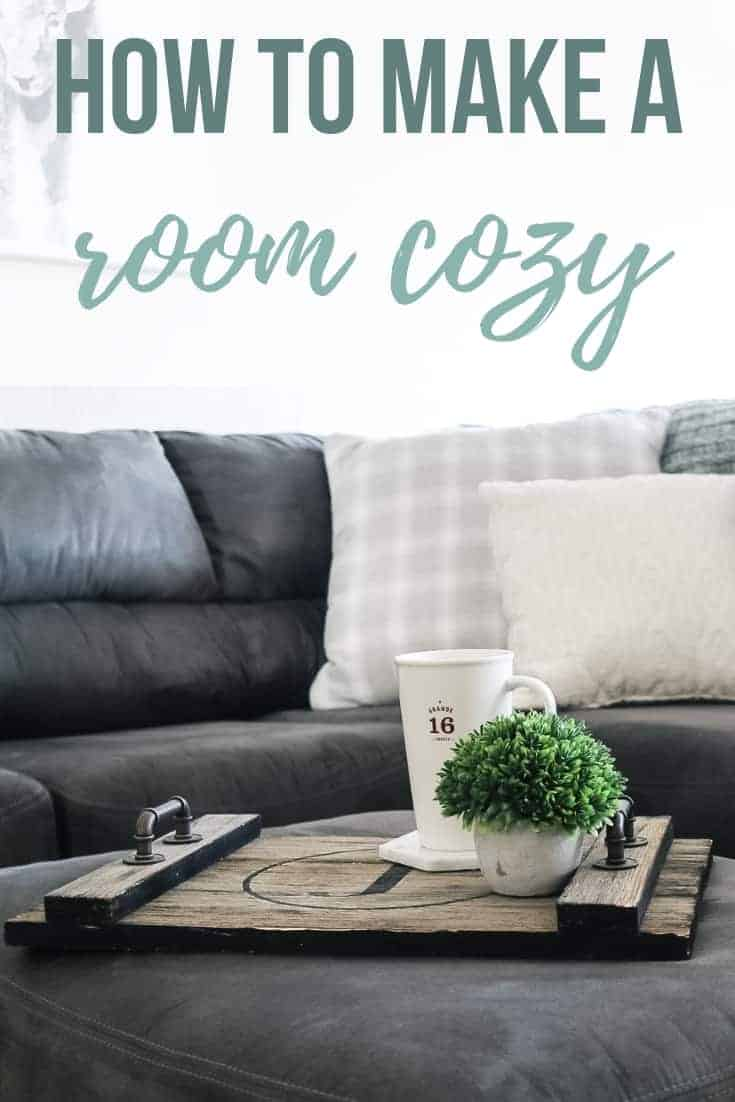Wooden tray with handles holding coaster, coffee cup and faux plant in concrete pot on gray ottoman in front of a gray sectional couch with light colored throw pillows and text overlay that says how to make a room cozy