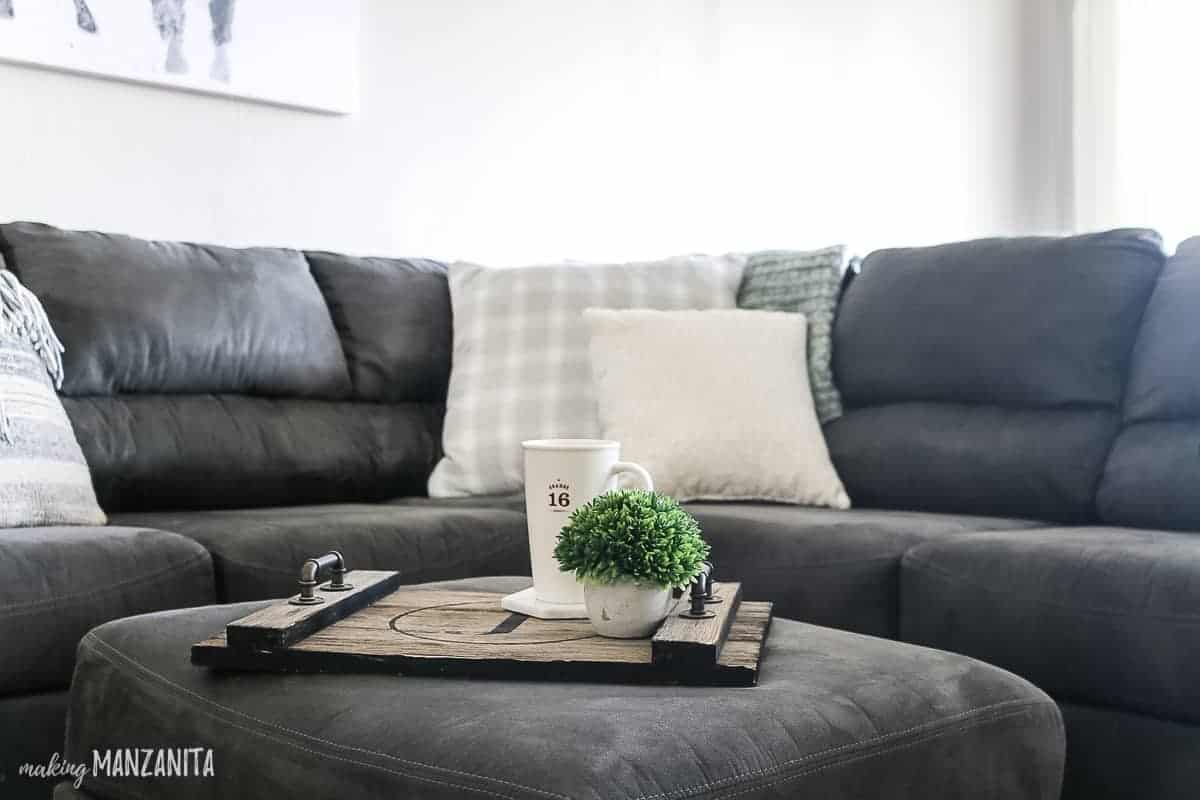 Wood tray on ottoman with coffee and plant in a cozy living room with gray sectional and neutral throw pillows
