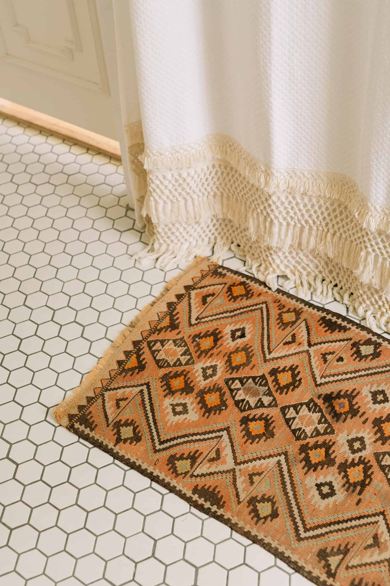 Tan southwestern looking vintage rug in a bathroom with white hexagon floor tile and macrame shower curtain
