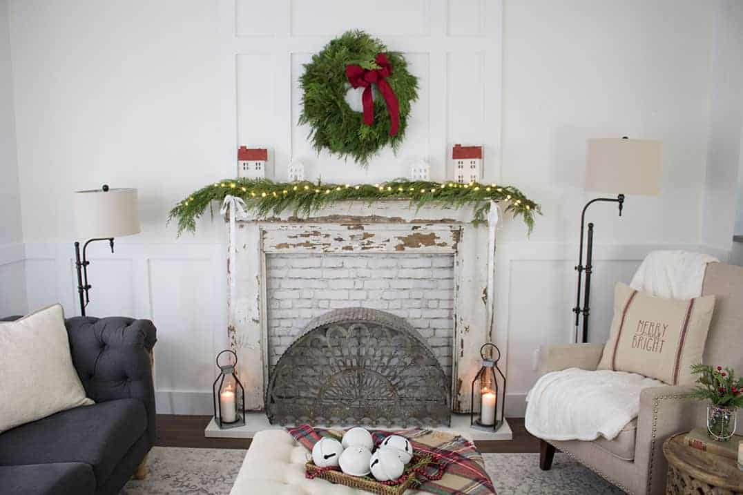 farmhouse decorated living room with christmas decorations featuring a vintage mantel with white chipped paint wood, greenery and lights and christmas wreath hanging above it. Two farmhouse floor lamps, a tan chair and dark gray couch are also shown in photo