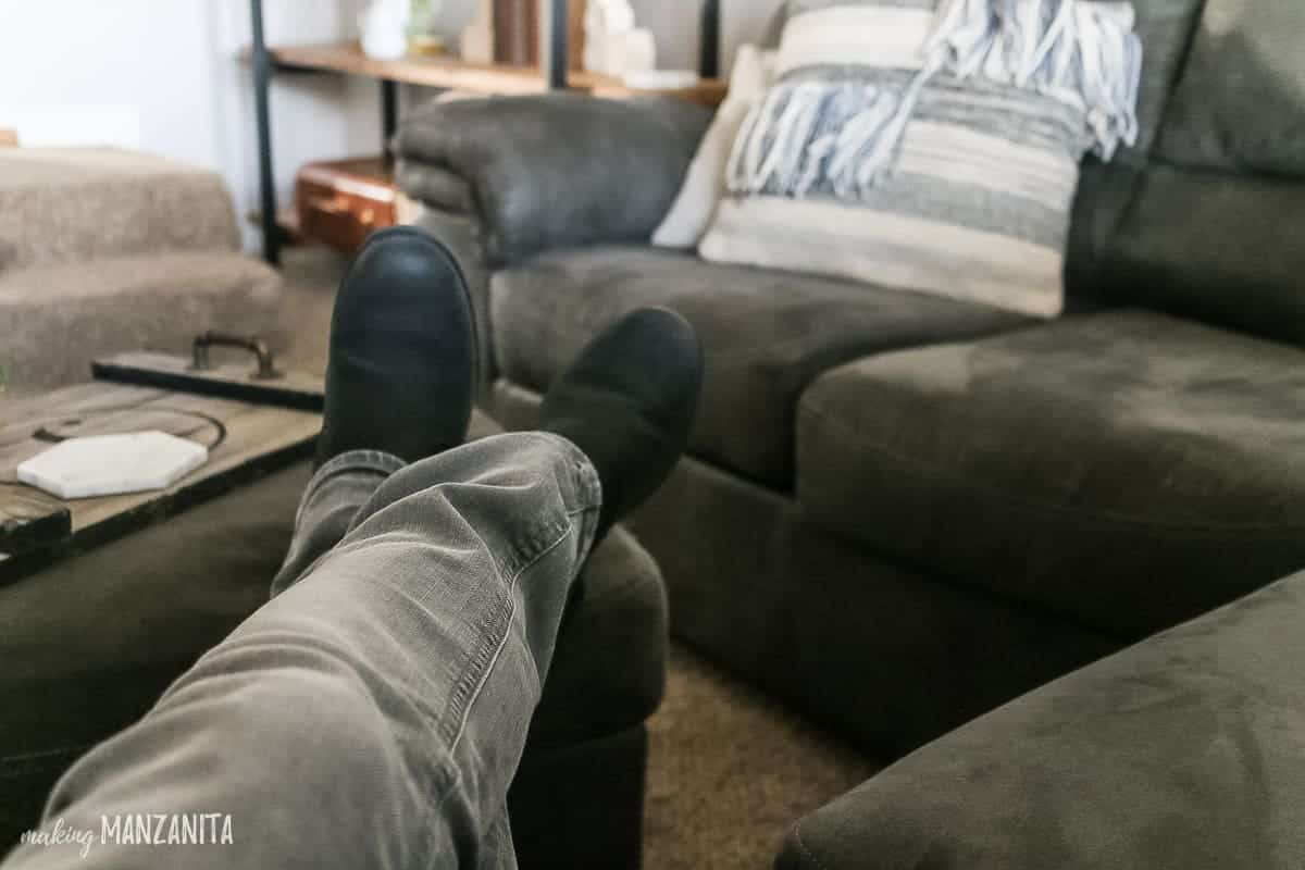 Feet lifted up on to a gray ottoman to show relaxing living room that is cozy
