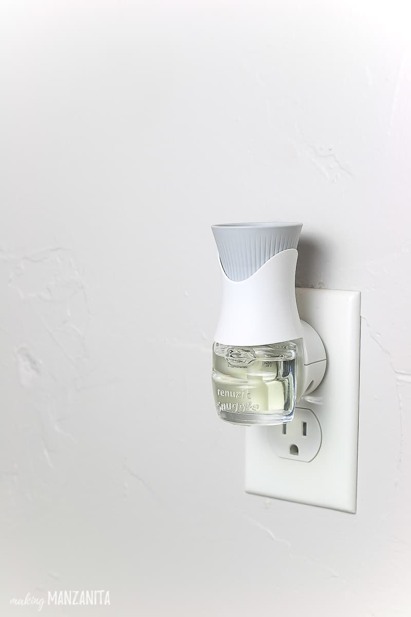 Plug in oil warmer with Renuzit Snuggle oil refill plugged into a wall with light gray paint
