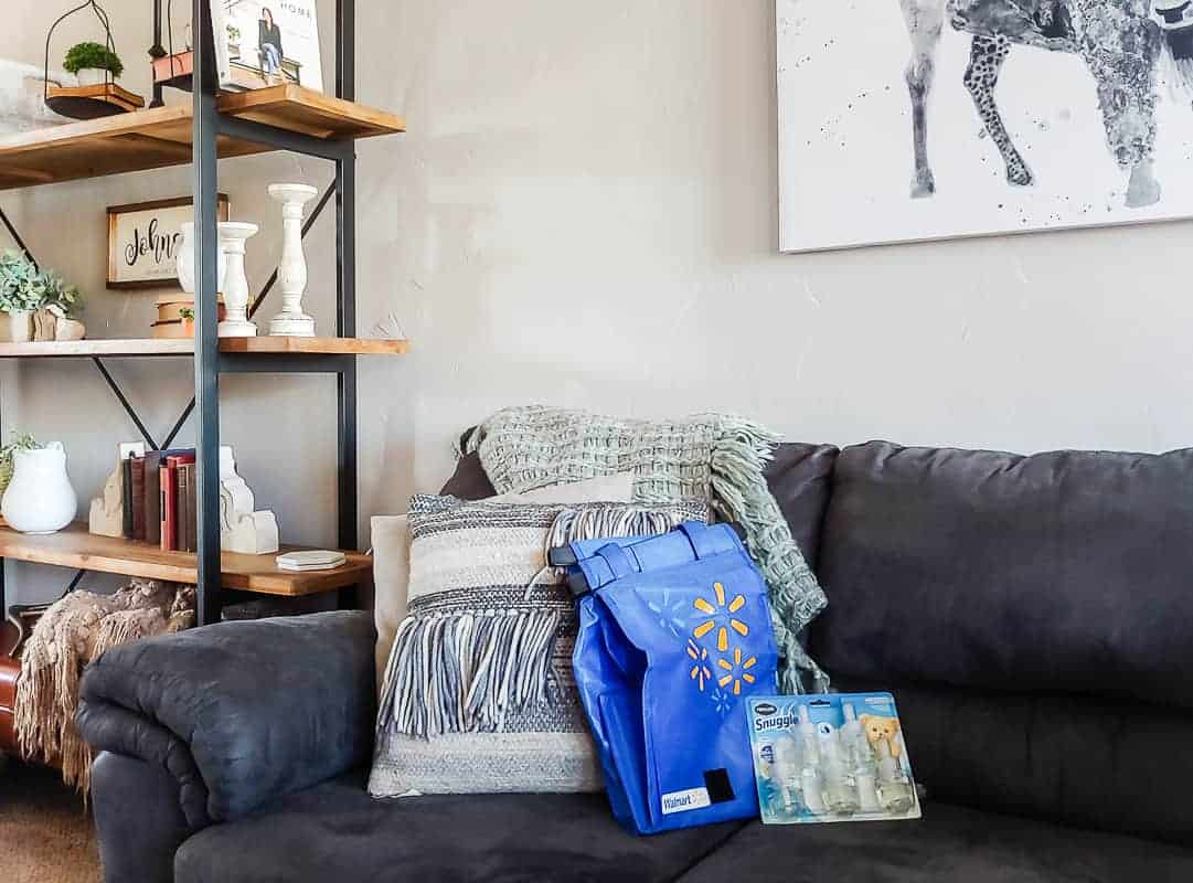 Reusable Walmart shopping bag on gray couch next to package of Renuzit Snuggle oil refills with modern farmhouse decor in the background