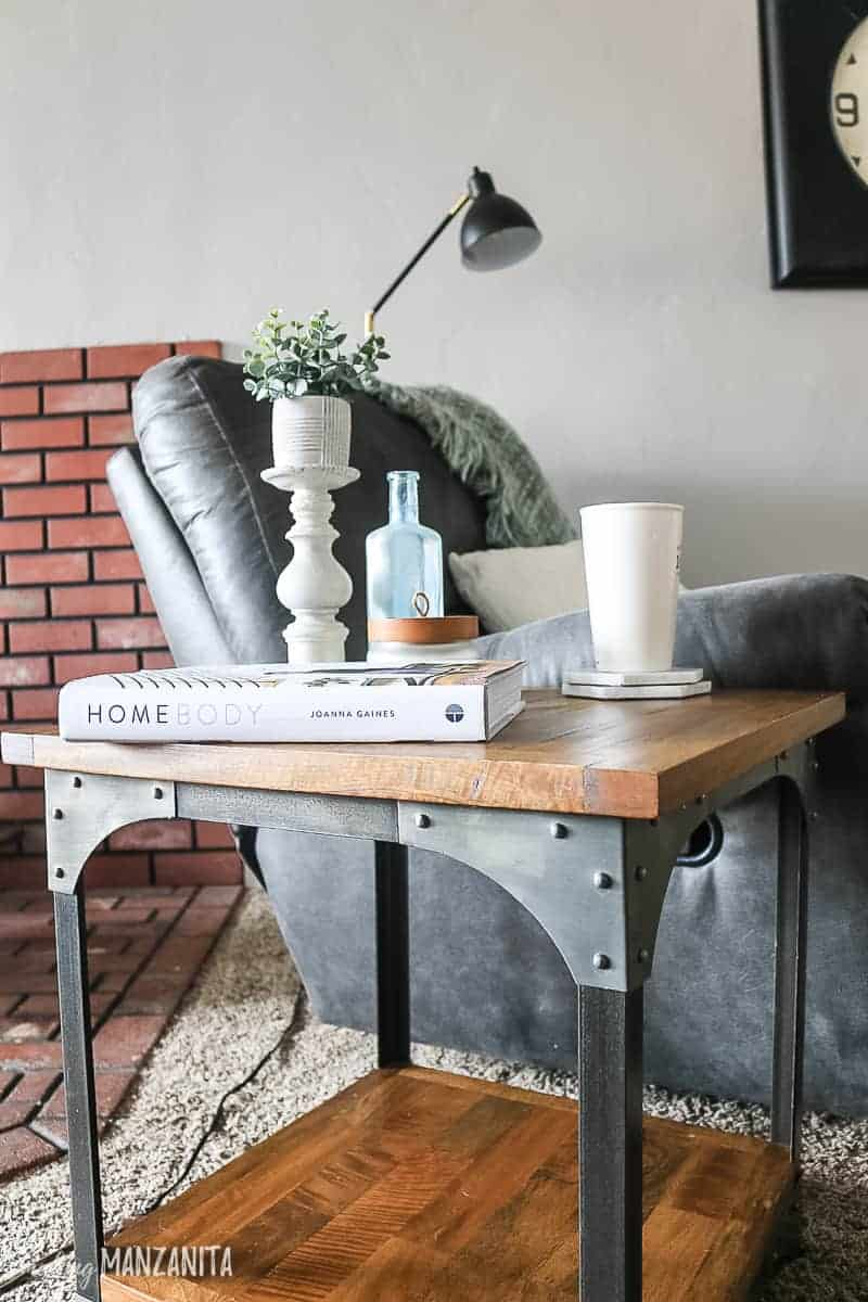 Rustic industrial side table next to recliner in cozy living room with farmhouse decor, candlestick with faux greenery, vintage glass bottle, Homebody book and cup of coffee on marble coaster on table, recliner with black floor lamp shown in background