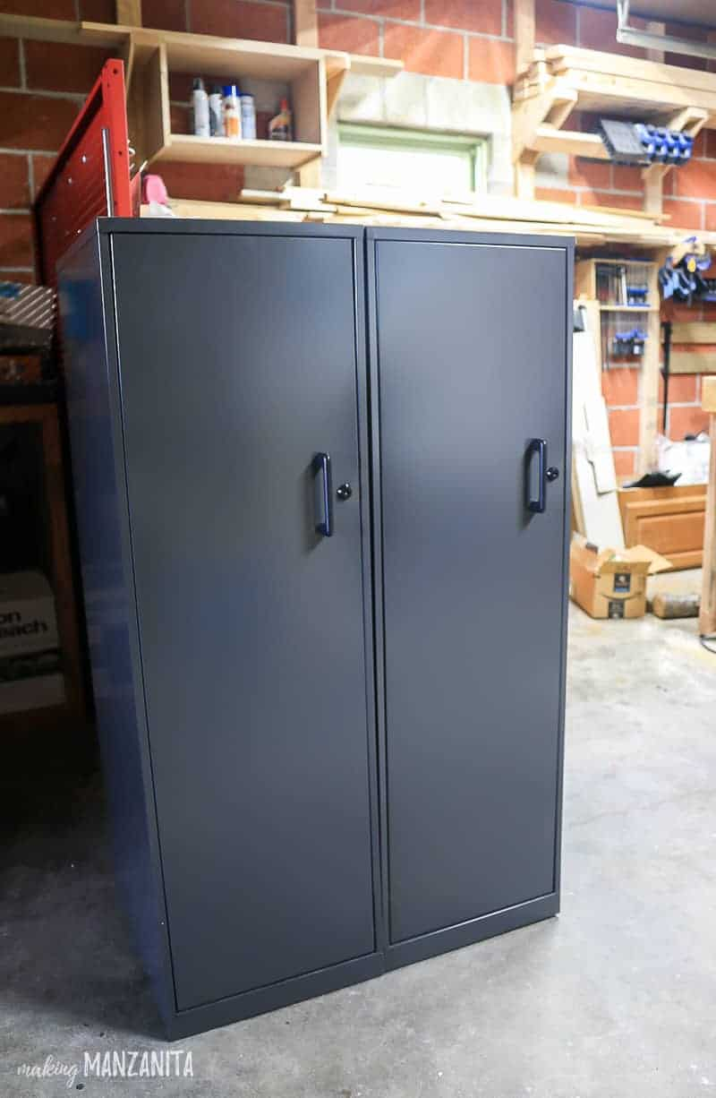 2 large gray cabinets with locks sitting side by side in a garage workshop area