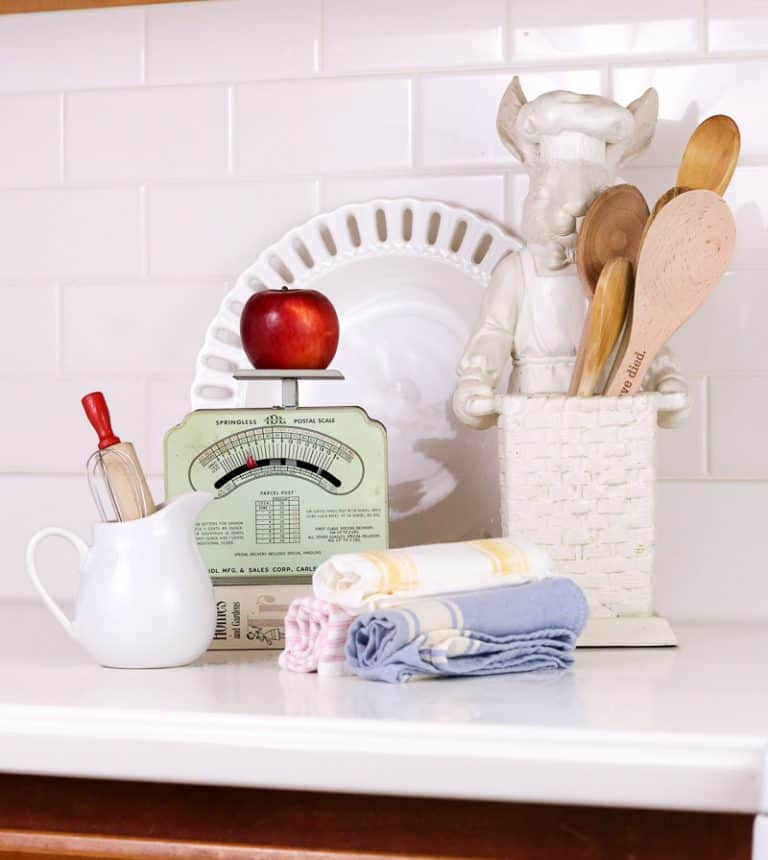 Vintage scale sitting on kitchen counter with red apple on it. Countertop also features white farmhouse pitcher, rolled hand towels, wooden spoons and white subway tile is shown in the background