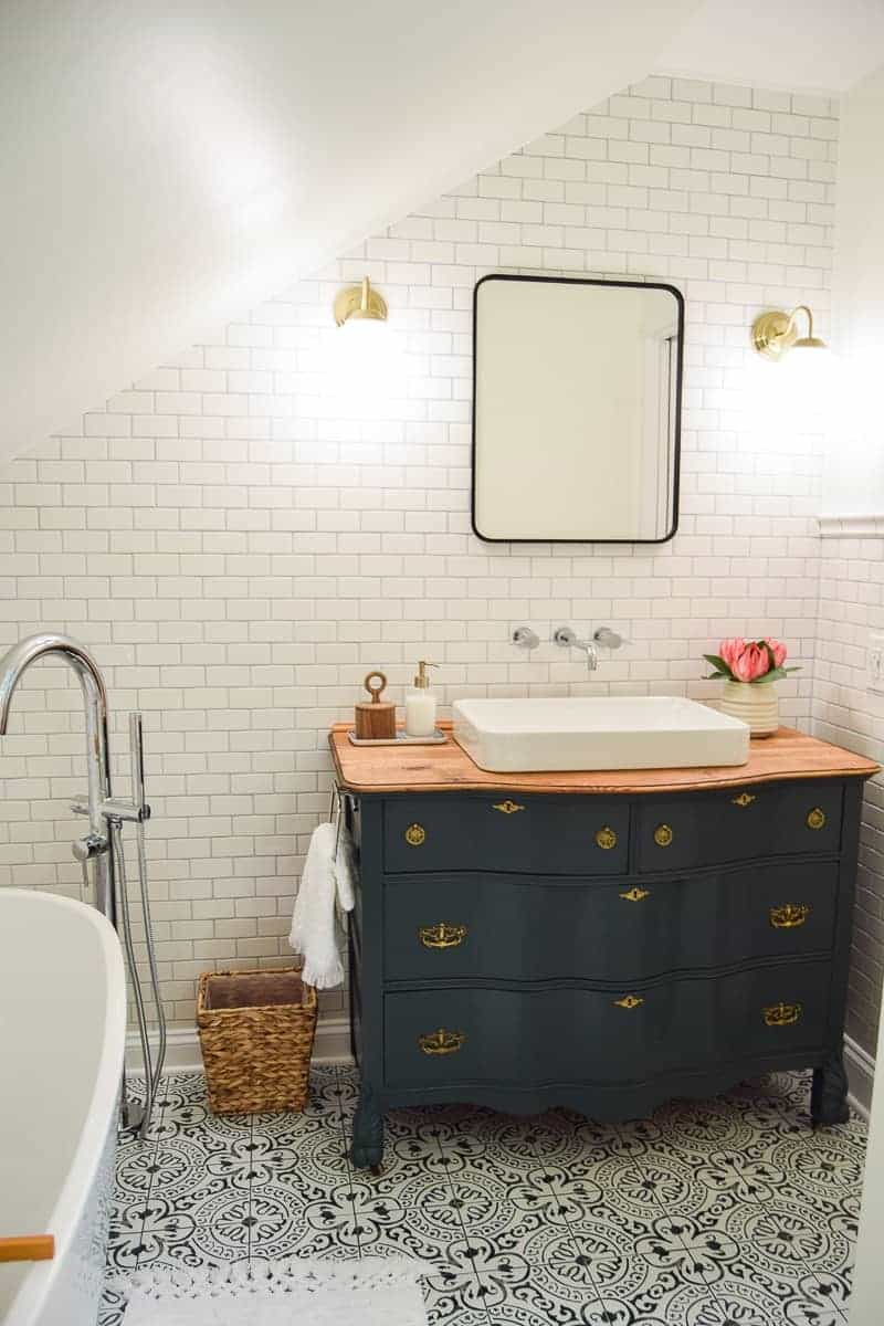 Bathroom showing blue painted vintage dresser used as vanity with a sink added, full wall of subway tile, cement tile flooring, modern globe lighting and metal framed mirror