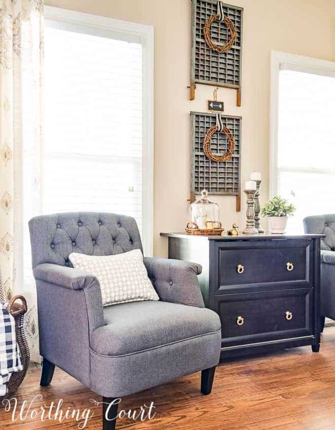 Vintage letterpress drawers hanging on wall with grapevine wreaths as wall decor with gray chair in front of window, tan pillow and black painted cabinet