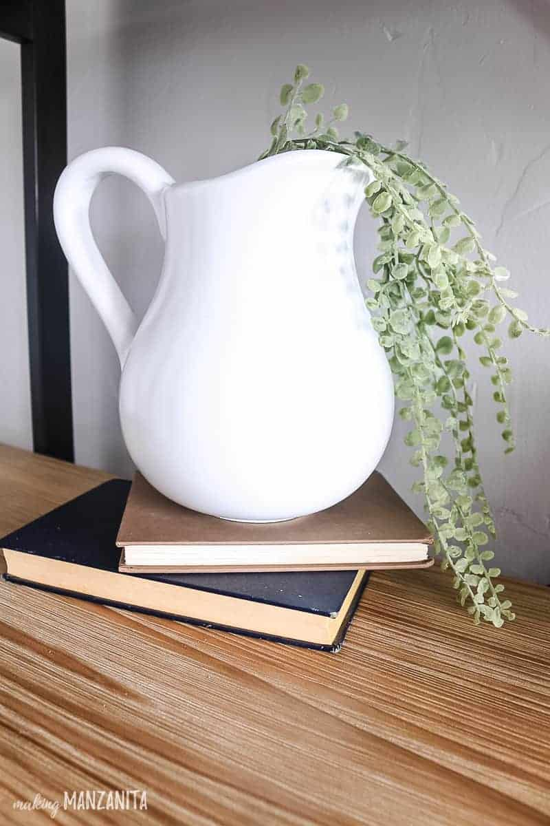 White farmhouse pitcher made by spray painting an old thrift store ceramic pitcher with a a high gloss white spray sitting on 2 vintage books stacked on a wooden shelf with faux greenery in it