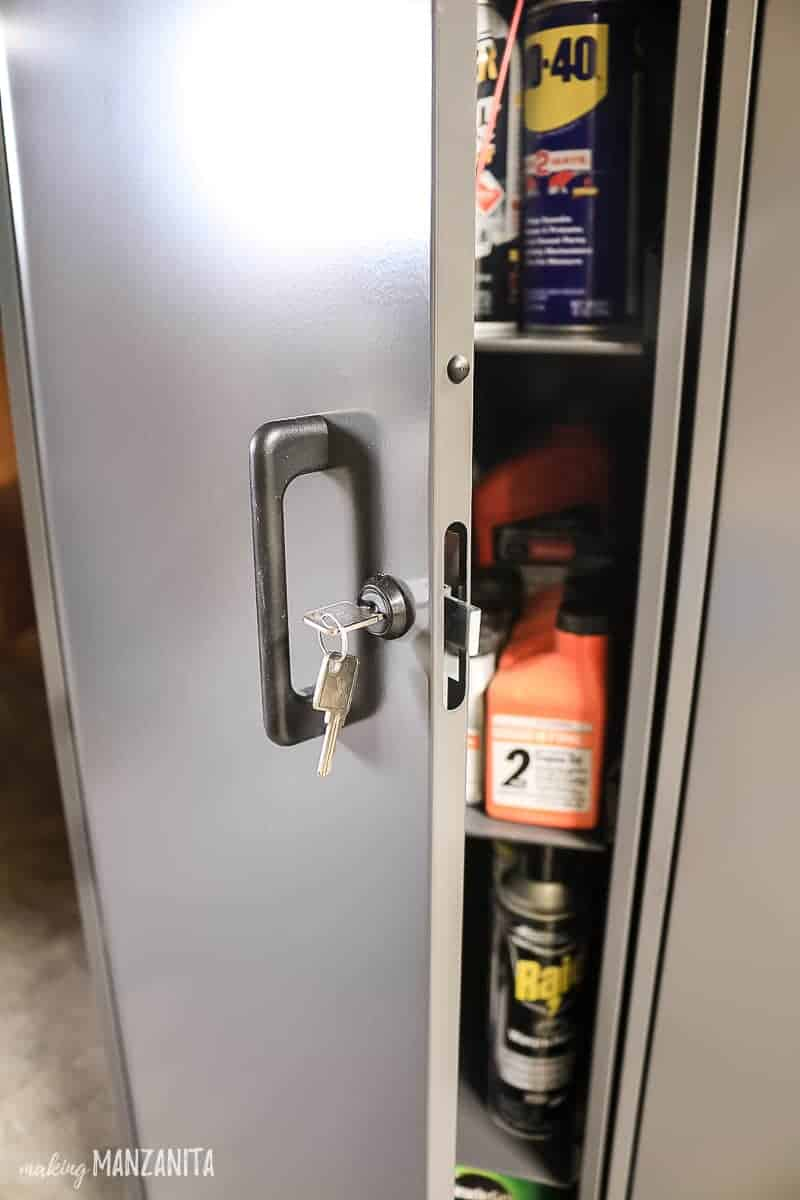 Handle and lock with key in it for a gray metal storage cabinet. Door is slightly open showing harmful chemicals like WD-40, engine oil and Raid pest control