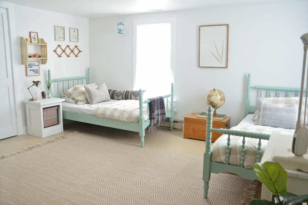 Vintage furniture painted mint green in a bedroom with two beds and other vintage decor pieces