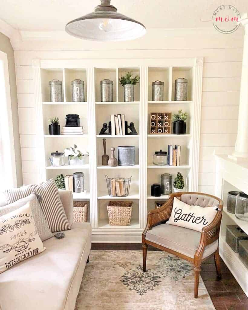 Built in shelves with vintage decor, books, baskets and farmhouse style decorations in a room with shiplap walls, industrial lighting and cream colored couch