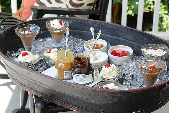 Ice cream sundae fixings in a metal tray cart with ice to keep cool on a porch
