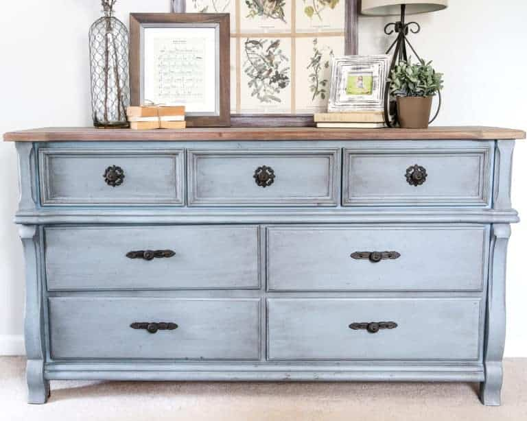 Gray blue painted vintage dresser with black hardware and farmhouse decorations on top