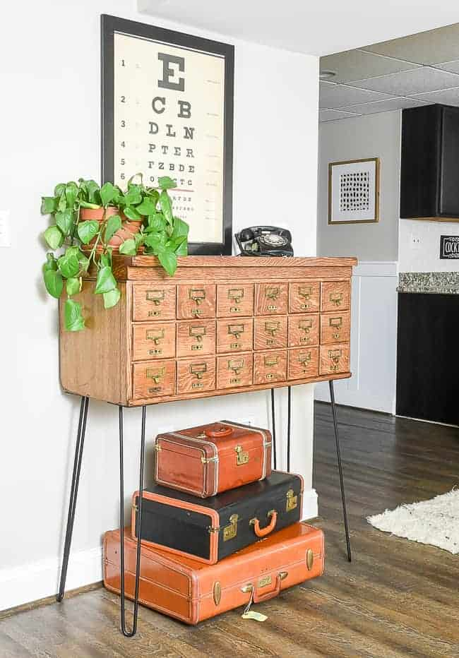 Vintage card catalog with hairpin legs restored and staged with old suitcases underneath, vintage eye chart as wall decor and plant and vintage telephone as decor