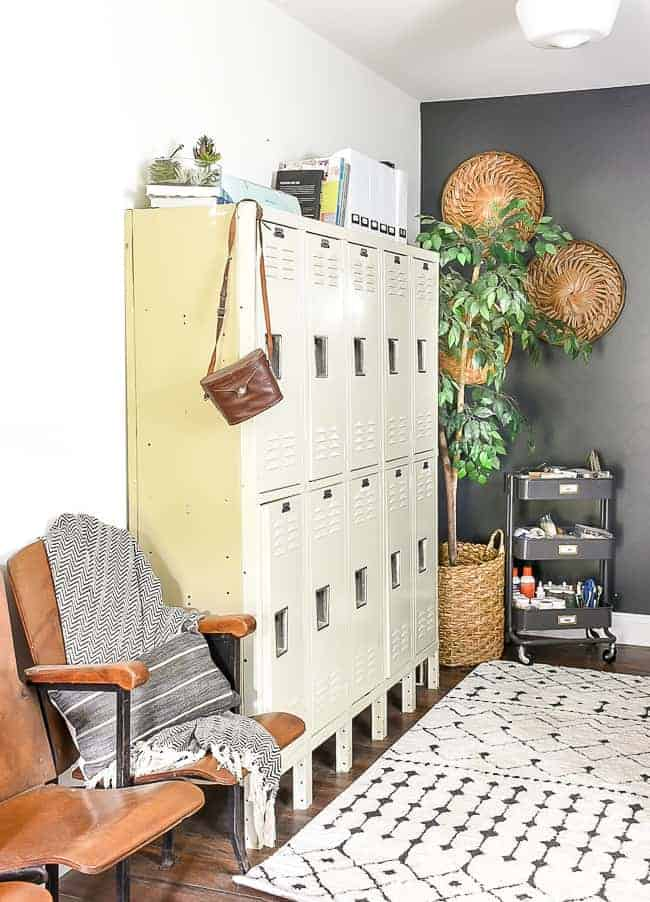 Office with a wall of pale yellow vintage lockers for storage, theater seating, boho run, baskets on wall and office supplies in rolling metal cart with ficus tree in the corner